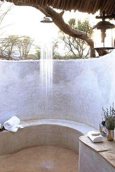 Diese schöne Dusche, erfrischt Sie mit einem einfachen, an einem Ast befestigten Duschkopf.