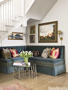 An upholstered banquette under foyer stairs sets a welcoming, relaxed, convivial tone.