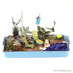 "Day at the Beach Fairy Garden ~ A relaxing and blissful summer scene! Succulents planted in an aqua enamel tray, with sand, gravel, and a scatter of deep blue sea glass to create the look of lapping waves. Accessories include a miniature table and chairs, shell garland, stepping stones, seashells, sand castle, birdhouse, and picnic basket. Created by Viviano Flower Shop with tiny items from the ""Gypsy Garden"" collection by Studio M and artist Genevieve Gail."