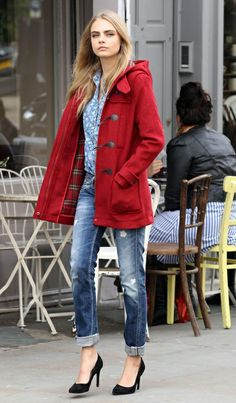 Winter style Cara. Blue patterned shirt, ripped jeans, red duffel coat, black heels.