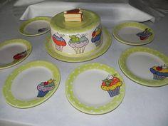 Boleira em cerâmica com 6 pratinhos de sobremesa, todos com desenhos de cupcakes.  Um jogo bastante colorido para alegrar o café da manhã ou o lanche da tarde. R$ 260,00