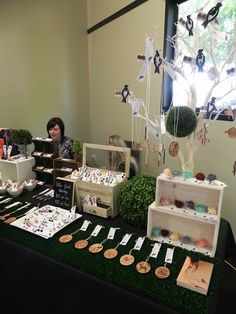 Astro-turf mat on top of table cloth with staggered box shelves and a tree for necklaces