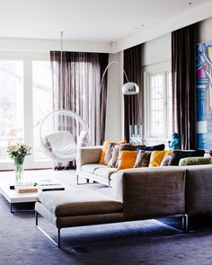 Love everything about this living room - low sitting sectional, big windows, Eero Aarnio bubble chair.