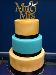 Blue, gold, and black fondant wedding cake. Made by Cosmopolitan Tea & Cafe in Puyallup, WA.