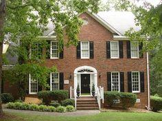 Red brick/black shutters/white trim. Paint door light green?