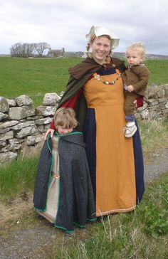 Photograph of a member of Sanday Soulka, on Orkney.  If you look very carefully she has a red underdress with long sleeves and the blue dress appears to be sleeveless with the straps just barely visible under the cloak but on top of the red dress. The apron dress side piece ends at the waist showing the blue dress.