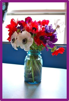 poppies in a mason jar with river rocks to help with arranging