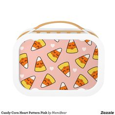 Candy Corn Heart Pattern Pink Lunch Box by NamiBear on Zazzle.com. This is a drawing of a candy corn with a smile on her face with hearts around her. It has a pink background.