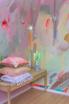 Vibrant abstract mural in pink, green and pastel colours, the energetic brushstrokes include a painted cactus. A neon cactus lamp glows on a wooden bench.