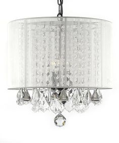 This beautiful chandelier touts three illuminating lights which are draped with crystals that capture and reflect the glow of the bulbs. A charming shade diffuses the excess radiance behind a gossamer whisper of a screen.