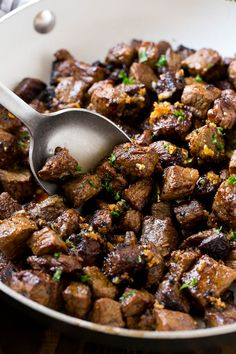 A pan of steak bites with a serving spoon.