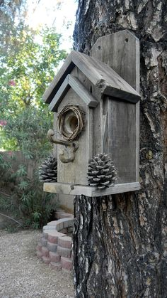 Here is a classic, rustic style that is easy to clean, and easy to mount. Two screws (included with your purchase) can easily attach this charming bird house to a tree or post. Made completely from rustic wood, and decorated with real pinecones from our yard plus a wreath around the bird hole, your birds are sure to feel right at home in any setting; whether its in a wooded area, at your cabin, or in your own back yard or patio. The perch is a metal coat hook, and there are drainage holes…