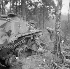BRITISH ARMY NORTH-WEST EUROPE 1944-45 (B 15052) Men of the 4th Royal Welsh Regiment construct a dug-out by the side of a knocked-out German StuG III assault gun near Weeze, 3 March 1945.