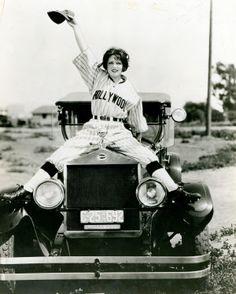 Actress Clara Bow straddling the hood of 1919 Moon in a baseball uniform. (1926)