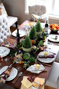 Need table setting ideas for Thanksgiving? Take a look at this casual yet elegant table dressed in rich plum tones, with greenery, artichokes, and gourds.