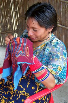 Kuna native stichting a reverse applique piece that was usually part of a young woman's dress bodice. Panama