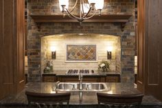This hearth style backsplash is the focal point of this kitchen.  Slate and travertine mixed with metallic accents gives this traditional design a modern feel.  #thetileshop