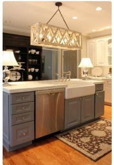 Beautiful gray feature island with a farm sink and the exact same light fixture I asked for. (Note the Java cabinets paired with the island).
