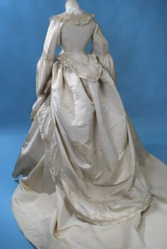 """Back, magnificent French 3 piece ivory silk faille reception/wedding gown dating to the third quarter of the 19thc. A marvel of fine French dress making construction and hand stitching, fascinating details through out all three pieces and made in the finest materials. With labels both on the waist petersham and the interior of one of the skirt's waist band, that reads """"Grands Magasins, Rue de la Paix""""."""