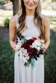 the maid of honor's unstructured  bouquet of  juliet garden rose, peach stock, burgundy dahlia, burgundy ranunculus, peach ranunculus, seeded eucalyptus, dusty miller, white lisianthus & lemon leaf.