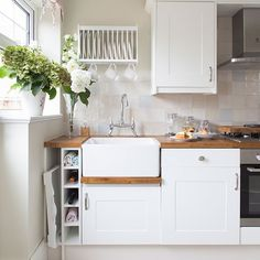 White units help to keep this small area feeling light and airy. Every space has been used to maximise on storage potential. The wooden worktops soften the look and give it a country feel, in keeping with the style of the rest of the house.  Similar sink Magnet Plate rack Tesco direct