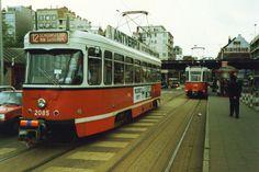 """De Franklin Rooseveltplaats, een PCC tram van ljn 12 rijdt richting Gemeentestraat, een PCC tram van lijn 11 rijdt naar de Melkmarkt. Op de achtergrond de """"ijzeren brug"""" over het kruispunt Frankrijklei - Kipdorpbrug, foto 1989."""