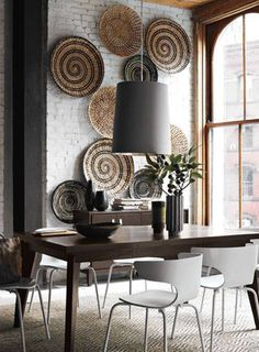 Woven baskets displayed on wall #diningroom tables, chairs, chandeliers, pendant light, ceiling design, wallpaper, mirrors, window treatments, flooring, #interiordesign banquette dining, breakfast table, round dining table, #decorating
