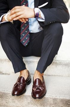 Pairing a dark grey suit and a baby blue dress shirt will create a powerful and confident silhouette. Feeling brave? Complete your look with oxblood leather tassel loafers.   Shop this look on Lookastic: https://lookastic.com/men/looks/suit-dress-shirt-tassel-loafers/17576   — White Pocket Square  — Light Blue Dress Shirt  — Navy Print Tie  — Charcoal Suit  — Burgundy Leather Tassel Loafers