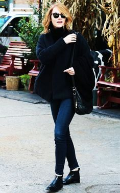 Emma Stone wears a turtleneck sweater, skinny jeans, ankle boots, and a black shoulder bag
