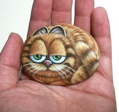 The Garfield Cartoon Cat Hand Painted Pebble! Painted with high quality Acrylic paints and finished with satin varnish. - Painted rocks Painted rocks Painted rocks Welcome to our website, We hope you are satisfied with th - Pebble Painting, Pebble Art, Stone Painting, Painted Rock Animals, Hand Painted Rocks, Painted Pebbles, Rock Painting Patterns, Rock Painting Designs, Garfield Cartoon