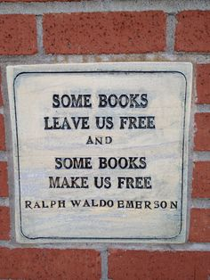 """Plaque embedded in exterior brick wall at Village Books in Fairhaven, Washington with a quote by Ralph Waldo Emerson; """"Some Books Leave Us Free and Some Books Make Us Free""""."""