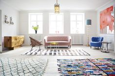 Wood floors and mix match rugs are a key to the scandi look.  Here it's been taken into vintage look with the softer upholstery
