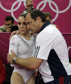 U.S. gymnast McKayla Maroney is contorted by a coach during the artistic gymnastics women's vault finals at the 2012 Summer Olympics, Sunday, Aug. 5, 2012, in London.