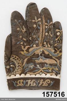 SE Östra Göinge. 1 udda handske av brunsvart sämskskinn fodrad med gråttt pälsfoder. På handens ovansida och vid tummenbroderi i blekta nyanser av blått, grönt rosa och vitt silke.
