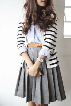 Light blue button down. Black and white cardigan. Grey pleated skirt