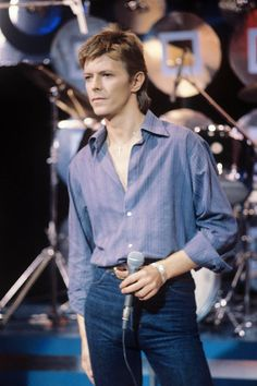 1977 A pared-down jeans-shirt ensemble for a performance on television programme Marc. After his theatrical Thin White Duke persona, Bowie moved to Berlin to rid himself of his drug additions and enjoy the city's thriving art and music scene. He adopted a more stripped-back look, leaving the glitter behind him.
