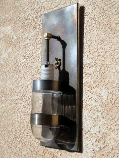 Recycled steel and glass lantern sconce.