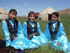 Kyrgyz girls in traditional dress sitting outside a yurt.