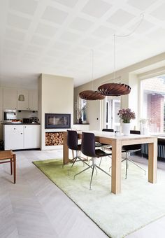 Large and open dining space with decorative pendants and a wooden dining table.