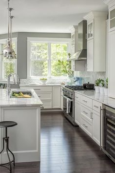 Gray and white kitchen features a white kitchen island topped with a white marble countertop seating a backless iron bar stool and completed with a sliding kitchen sink cutting board and 2 polished nickel gooseneck faucets.