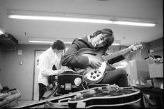 George Harrison tunes his guitar.
