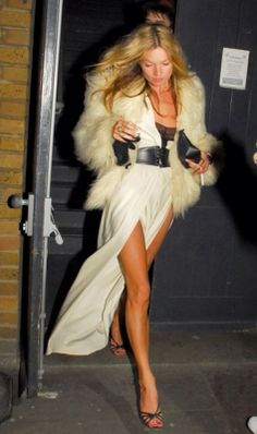 Kate Moss shows off her tanned legs in split maxi dress and fur coat.