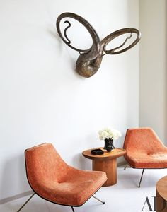 Trope Heroic by Terry Adkins looms above a pair of vintage James Donahue chairs in the living room of powerhouse gallery owner Dominique Lévy and movie producer Dorothy Berwin's Hamptons home | archdigest.com