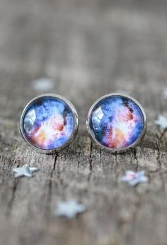 This is a pair of handmade galaxy stud earrings. These earrings were made with high quality galaxy prints and 12 mm clear glass domes. They are attached to 14 mm ( roughly 1/2 inch) silver earring stu