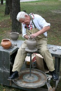 old guy at a potters wheel with pots in background