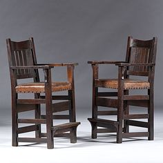 "Gustav Stickley Billiard Chairs American, early 20th century, a pair of ""V"" back billiard chairs in oak, each having five vertical back slats, tacked leather seats, original finish,"
