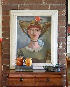 A self-portrait of Dorothy Eisenbach displayed against the brick wall is among John's favorite paintings in his eclectic mix of original art.