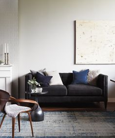 A modern sofa has understated elegance upholstered in the softest charcoal-coloured wool and layered with luxe cashmere pillows. An over-dyed wool rug and jewel-toned accessories inject subtle colour,