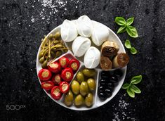pletter appetizer of green olives, black olives, capers, buffalo - pletter appetizer of green olives, black olives, capers, buffalo mozzarella, artichokes and red Chili peppers filled with tuna on black marble