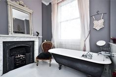 beautiful grey bathroom with 13ft ceilings in a mid-19th century London Victorian. claw foot tub with black painted exterior. black fireplace with marble mantle and surround. beautiful white antique mirror on the mantle. purplish-grey. grey-purple walls and curtains. vintage antique chair seating in the bathroom, i love seating in a bathroom!! ...the house is for sale for 3million.